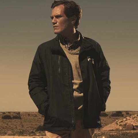 michael shannon in a still from 'waco' he is standing in a deserted landscape presumably, what is meant to be waco, texas, staring into the distance onhis right