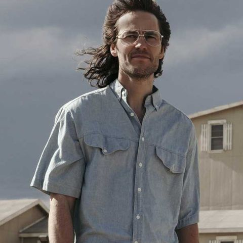 taylor kitsch appearing as david koresh in 'waco' series he's starring off into the distance, in front of his compound