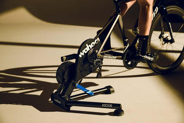 a stationary bike trainer connected to a road bike rear end