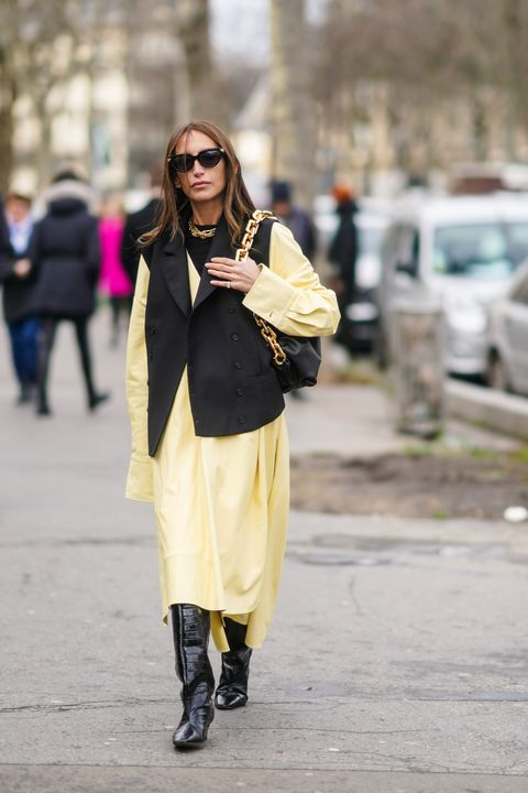 paris, france   february 26 chloe harrouche wears sunglasses, a necklace, a black vest, a light yellow asymmetric flowing dress, black crocodile pattern boots, a black bag with a large gold chain strap, outside mugler, during paris fashion week   womenswear fallwinter 20202021, on february 26, 2020 in paris, france photo by edward berthelotgetty images
