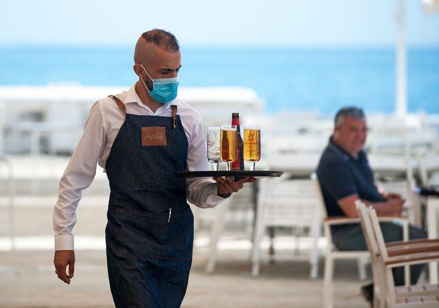 a waiter serving beer to customers at 'los baños del carmen