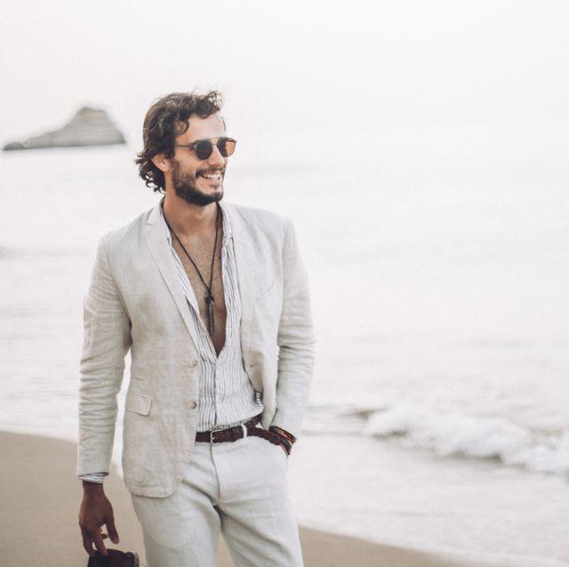 un hombre con barba paseando por la playa