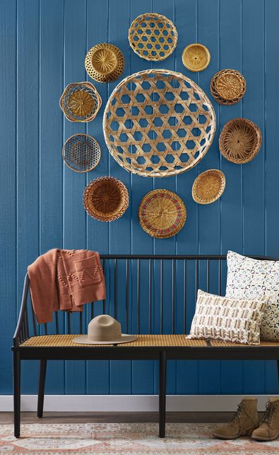 baskets of all styles arranged on a wall that is painted blue with a bench in front of it
