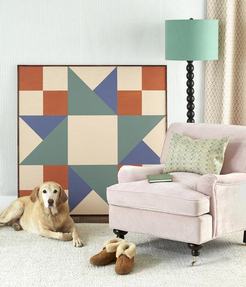 a large piece of artwork in a geometric quitl square shape propped up on a wall by a chair lamp and dog