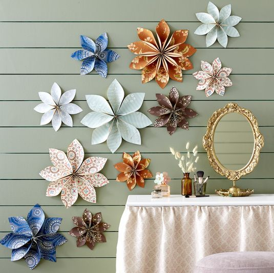 flowers made of colorful wallpaper hang on a wall above a vanity