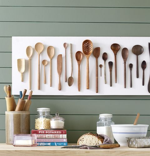 wooden spoons from light to dark hung on a kitchen wall