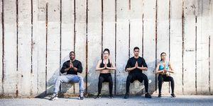 Vier mensen doen een wall sit