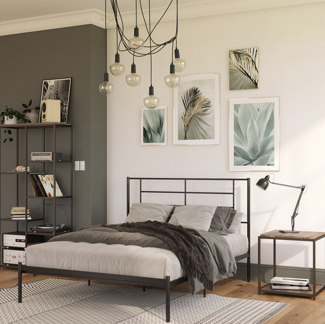 bedroom with black bed frame, light pendant, side table with lamp, gallery wall with botanical prints, and rug