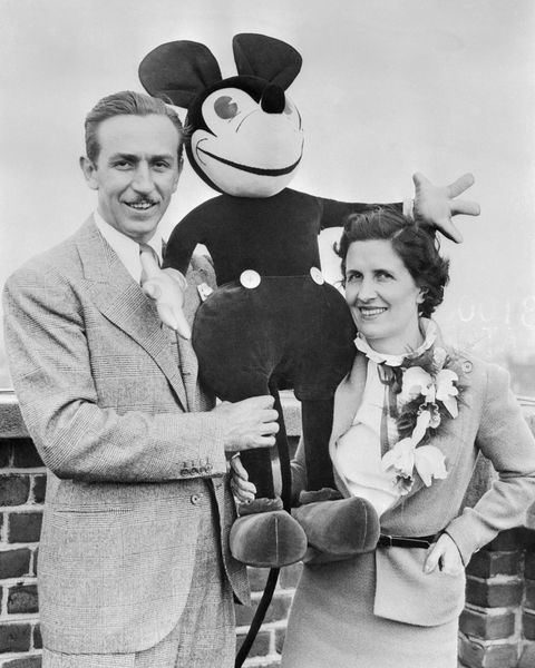 walt and mrs disney standing with stuffed mickey mouse