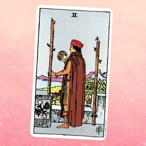 the tarot card the two of wands, showing a person in a tunic, cape, and robe, holding a glass ball they're standing between two wooden staffs, looking out at a view of a mountain and a body of water