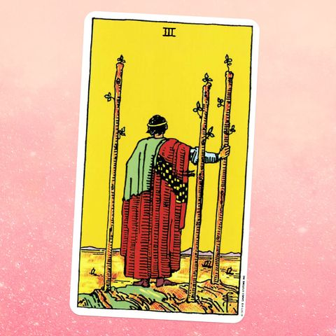 the tarot card the three of wands, showing a person in robes holding a wooden staff and looking off into the distance, with two more staffs next to them