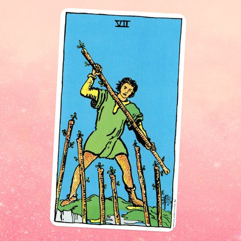 the seven of wands, showing a person in a green tunic and yellow leggings, holding a staff as if ready to fight six more staffs are raised up in front of them