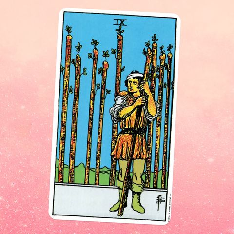 the tarot card the nine of wands, showing a person in aa tunic holding a wooden staff with eight more behind them