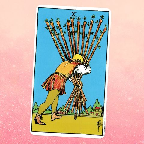 the ten of wands tarot card, showing a man from behind, holding a pile of ten giant wooden sticks in his arms