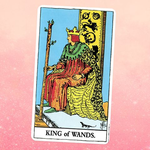 the tarot card the king of wands, showing a man in a robe, cape, and crown sitting on a throne, holding a wooden staff