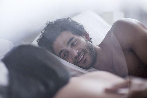 Man vertelt een vrouw iets terwijl ze in bed liggen