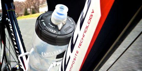 Fluid, Liquid, Bottle, Plastic bottle, Logo, Water bottle, Bottle cap, Drinkware, Bicycle wheel rim, Gas,