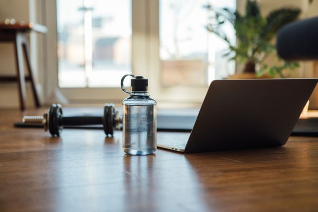 water bottle, dumbbell, exercise mat and laptop on the floor