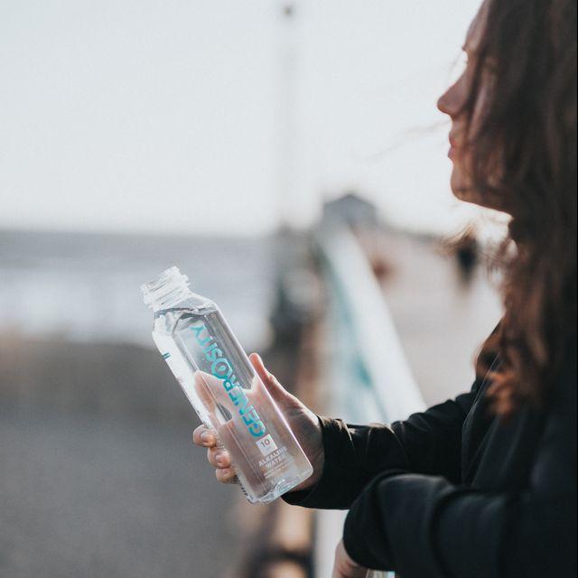 vrouw drinkt water op het strand