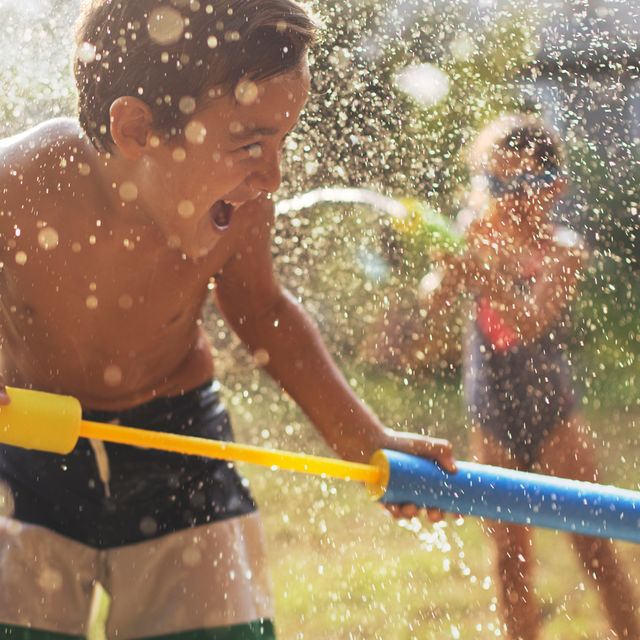 kids playing with water guns in yard