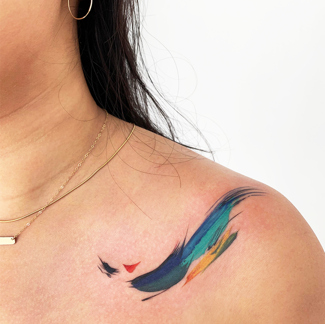watercolor tattoo ideas   photo description side by side images of a woman with a watercolor tattoo on her shoulder and another woman with a watercolor tattoo in green and blue on her back