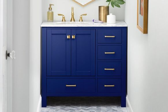 blue bathroom vanity with gold hardware and marble top