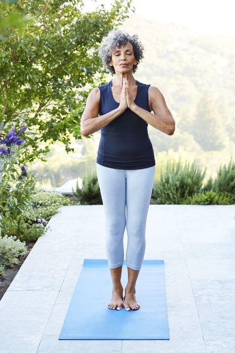african american senior doing yoga standing with hands in the prayer position