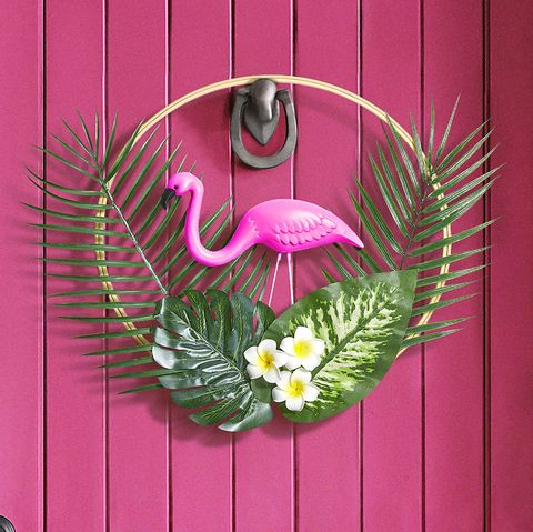 a tropical pink front door with a flamingo wreath