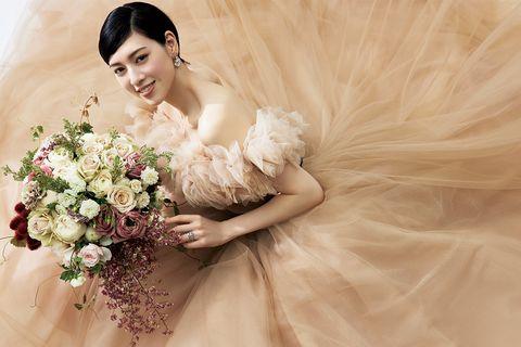 「ハツコ エンドウ ウェディングス」のベージュカラーのドレスに大きなブーケをあわせた三吉彩花