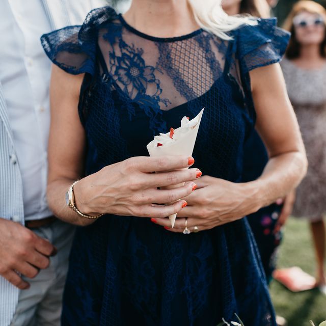 wedding guest in navy lace dress holding confetti