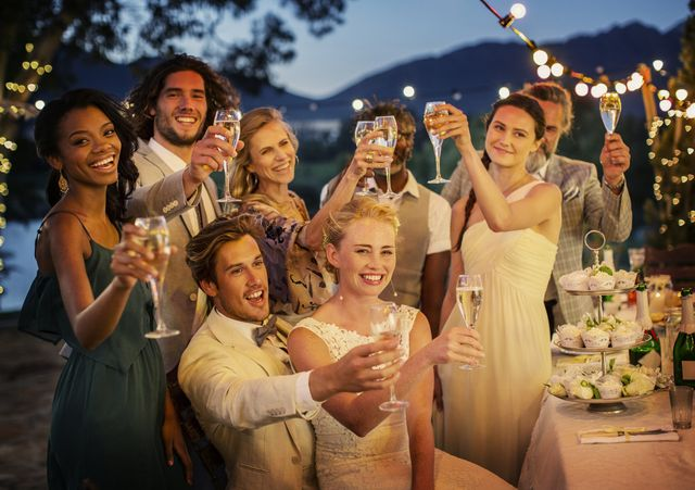 a bride and groom and wedding guests toasting champagne