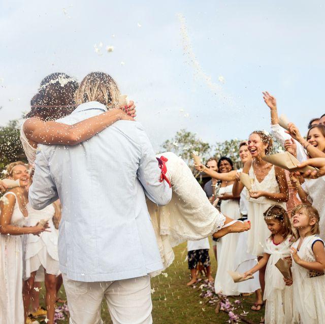 invités au mariage jetant du riz aux jeunes mariés, à l'extérieur