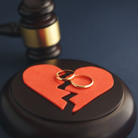 Wedding rings on the figure of a broken heart from a tree, hammer of a judge on a wooden background. Divorce