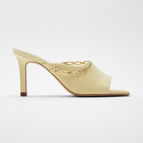 creamvery pale yellow mules with thin heel and thin gold chain attached the front of the shoe