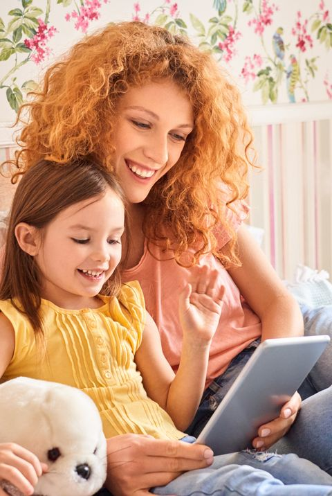games to play on zoom - Weekend Concept. Mother and daughter ling on bed at home having video call on digital tablet laughing cheerful