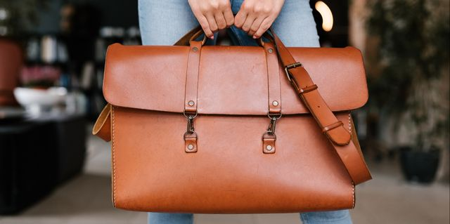 woman holding leather weekender bag