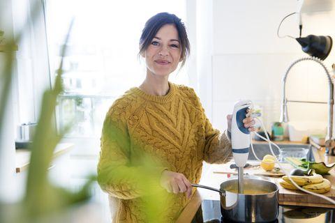 vrouw maakt soep in de keuken