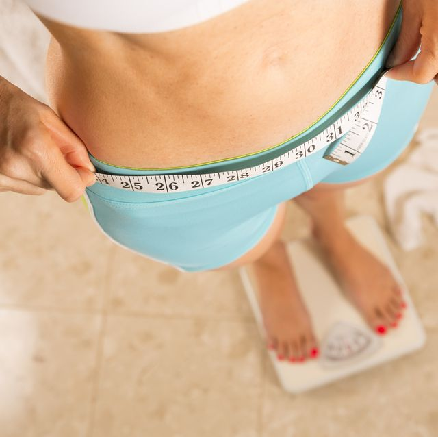 healthy lifestyle weight conscious woman with measuring tape around waist