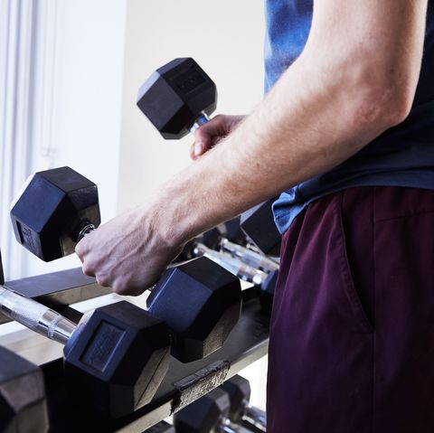 chest exercises, man picking up dumbbells to prepare for chest exercises