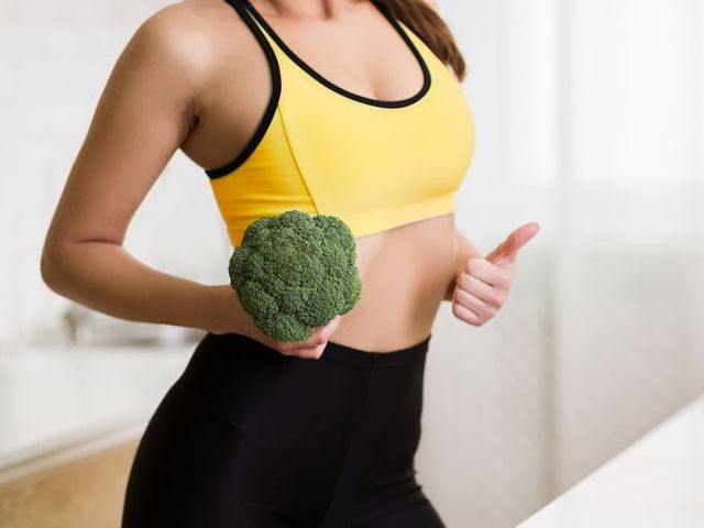Weight loss concept. Girl holding broccoli and showing thumb up