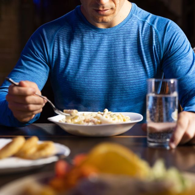 close up of athlete eating pasta dish