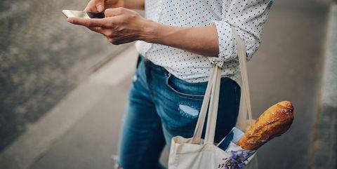 Vrouw met boodschappentas met stokbrood