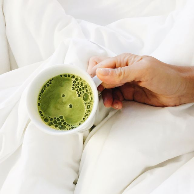 hand holding mug of matcha over white blanket
