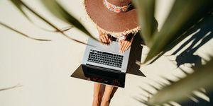 vrouw op haar laptop op het strand