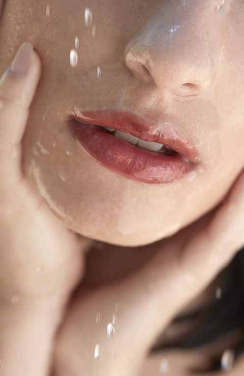 wet brunette woman with make up having a shower in sunlight lips detail