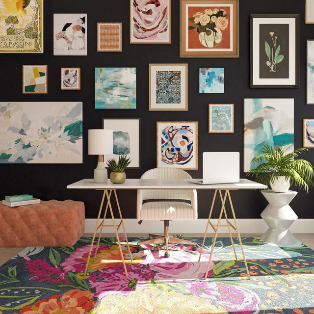 home office with colorful prints on black wall, desk, and chair