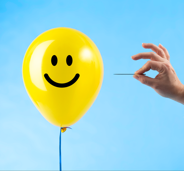 toxic positivity popping yellow balloon with smile face