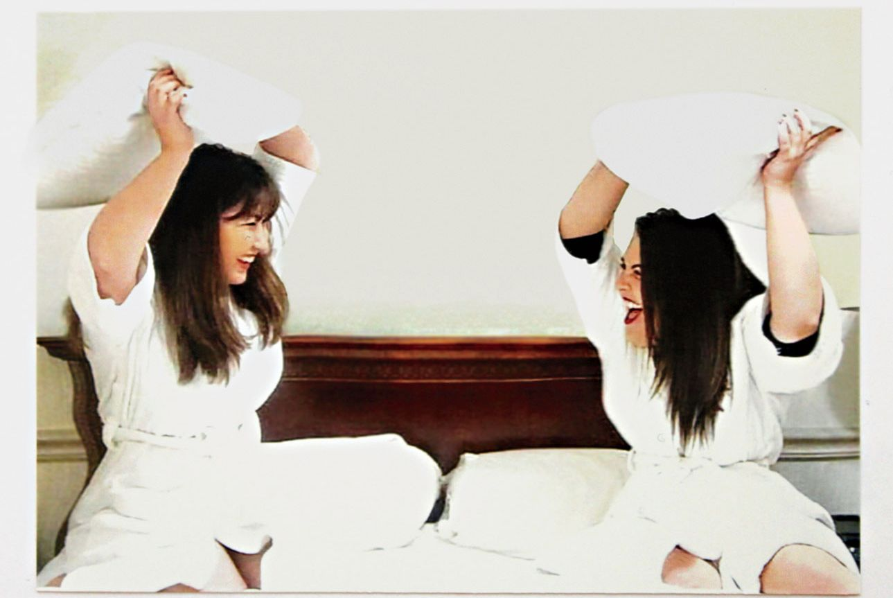 Karen Hopkins and Alexandra Booze wearing robes in a bed pillow fight