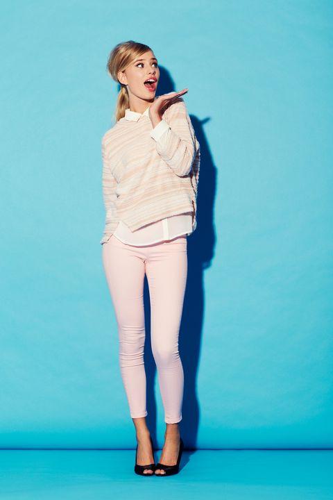 una mujer joven con un conjunto rosa con cara de sorpresa