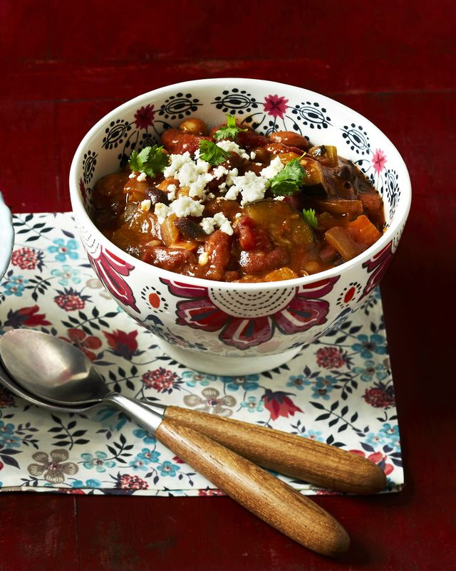 veggie chili with cotija cheese on red wood board two bowls